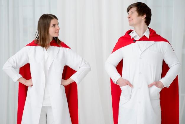 Vue de face des médecins posant avec des manteaux