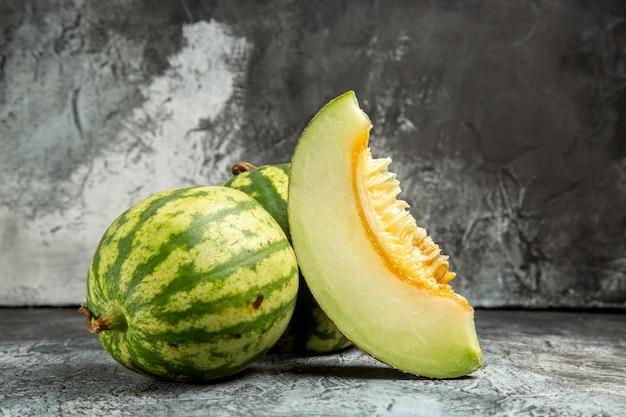 Vue de face de melon frais avec de la pastèque sur le fond sombre-clair