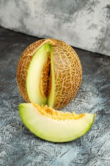 Vue de face de melon frais tranché sur plancher sombre-clair doux fruits d'été moelleux