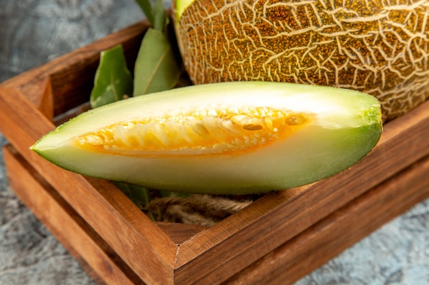 Vue de face de melon frais en tranches sur fond sombre-clair