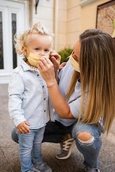 Vue de face de la mère et de l'enfant avec des masques médicaux