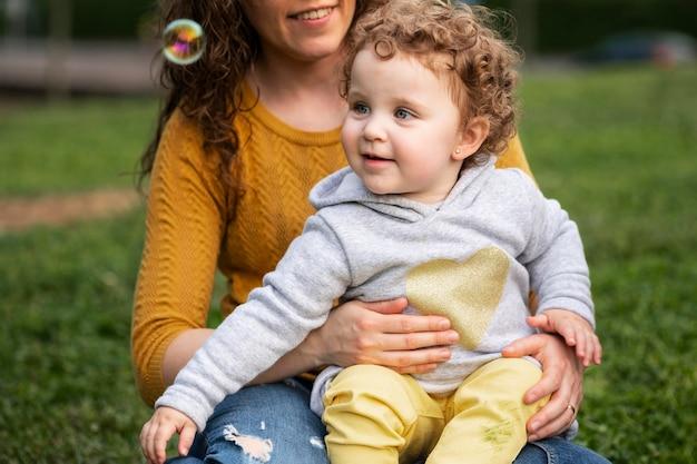 Vue de face de la mère lgbt à l'extérieur dans le parc avec son enfant