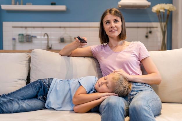 Vue de face mère regardant la télévision pendant que son fils dort