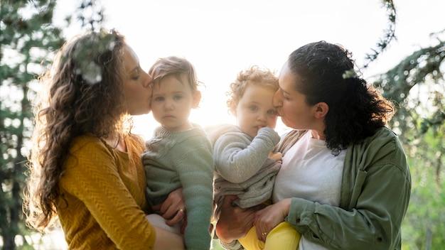 Vue de face des mères lgbt à l'extérieur dans le parc avec leurs enfants