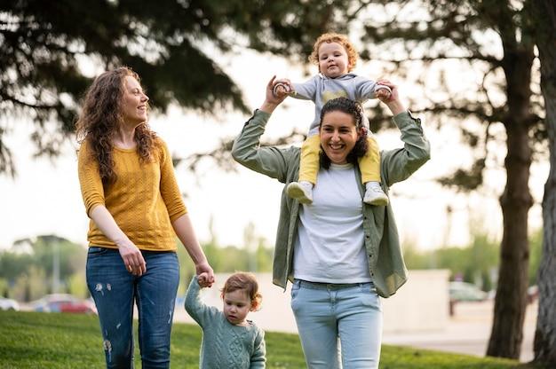 Vue de face des mères lgbt smiley à l'extérieur dans le parc avec leurs enfants