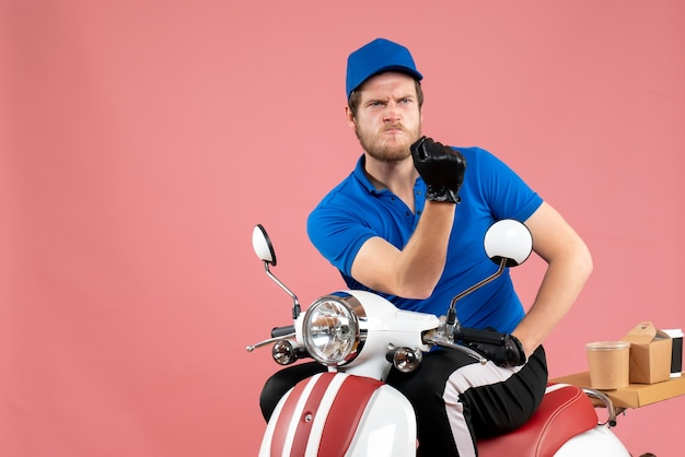 Vue de face messager masculin en uniforme bleu sur la livraison de vélo de nourriture rose travail de couleur service de restauration rapide