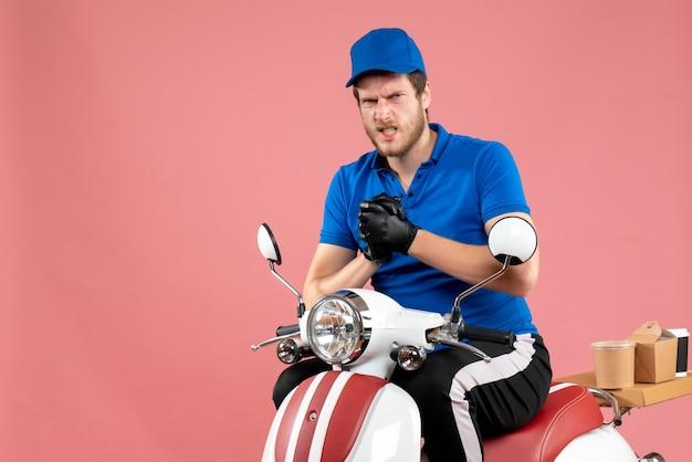 Vue de face messager masculin en uniforme bleu sur le service de couleur de travail de livraison de vélo de restauration rapide de nourriture rose