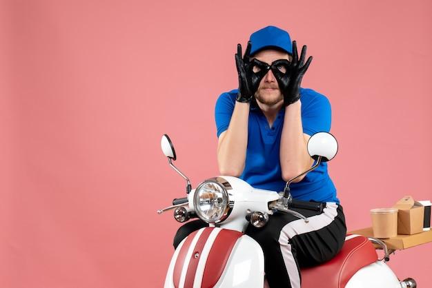 Vue de face messager masculin en uniforme bleu sur un service de travail de couleur de travail de livraison de vélos de restauration rapide de nourriture rose