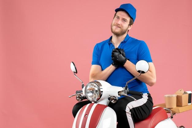 Vue de face messager masculin en uniforme bleu sur le service de travail de livraison de vélo de nourriture rose service de restauration rapide