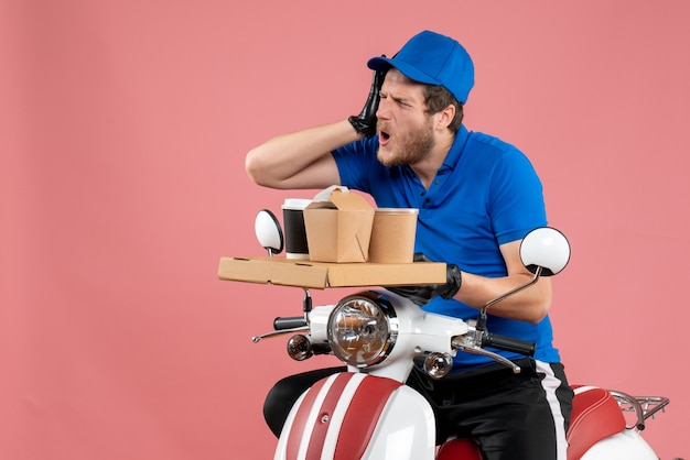 Vue de face messager masculin en uniforme bleu tenant une boîte de café et de nourriture sur la couleur du vélo de livraison de travail de restauration rapide de service rose