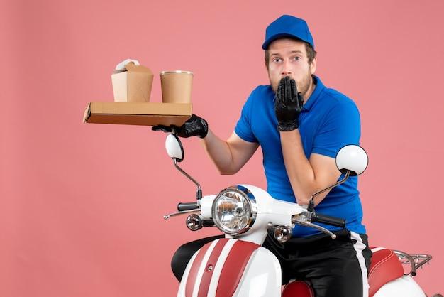 Vue de face messager masculin en uniforme bleu tenant une boîte de café et de nourriture sur la couleur du vélo de travail de livraison de restauration rapide de service rose