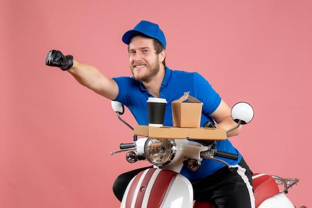 Vue de face messager masculin en uniforme bleu tenant une boîte de café et de nourriture sur le service rose travail de restauration rapide livraison couleur vélo