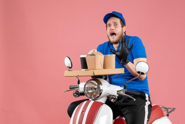 Vue de face messager masculin en uniforme bleu tenant une boîte de café et de nourriture sur un vélo de travail de livraison de travail de restauration rapide de service rose