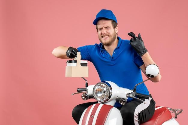 Vue de face messager masculin en uniforme bleu tenant un café sur un travail de couleur de travailleur de vélo de livraison de restauration rapide rose