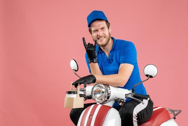Vue de face messager masculin en uniforme bleu tenant un café sur un travail rose couleur de travailleur de service de vélo de livraison de restauration rapide