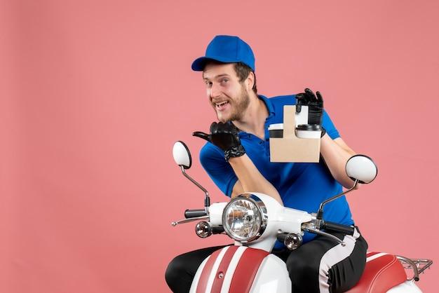 Vue de face messager masculin en uniforme bleu tenant un café sur un vélo de travail de livraison de travailleur de restauration rapide de couleur rose
