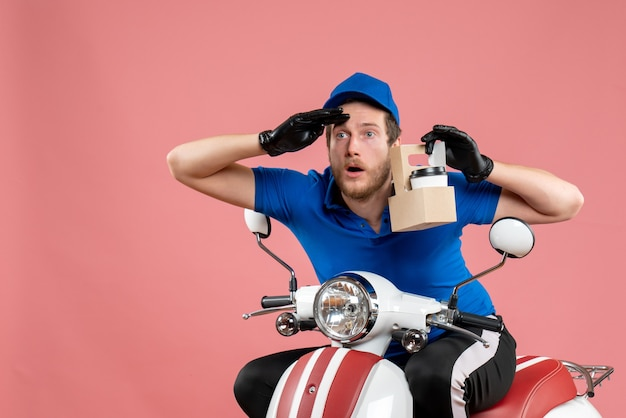 Vue de face messager masculin en uniforme bleu tenant un café sur le vélo de travail de livraison de travailleur de service de restauration rapide de couleur rose