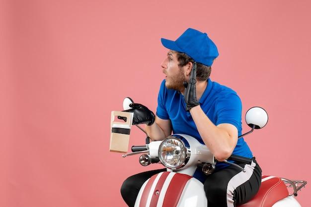 Vue de face messager masculin en uniforme bleu tenant un café sur un vélo de travail de service de livraison de restauration rapide de couleur rose