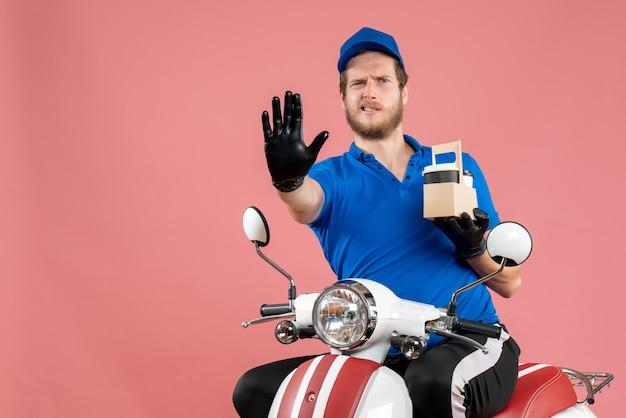 Vue de face messager masculin en uniforme bleu tenant un café sur le vélo de travail de travailleur de service de livraison de restauration rapide de couleur rose
