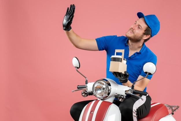 Vue de face messager masculin en uniforme bleu tenant un café sur un vélo de travail de travailleur de service de restauration rapide de couleur rose