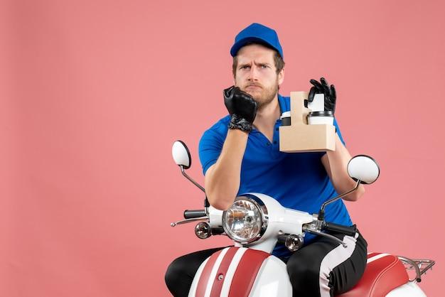 Vue de face messager masculin en uniforme bleu tenant un café sur un vélo de travailleur de service de livraison de restauration rapide de couleur rose