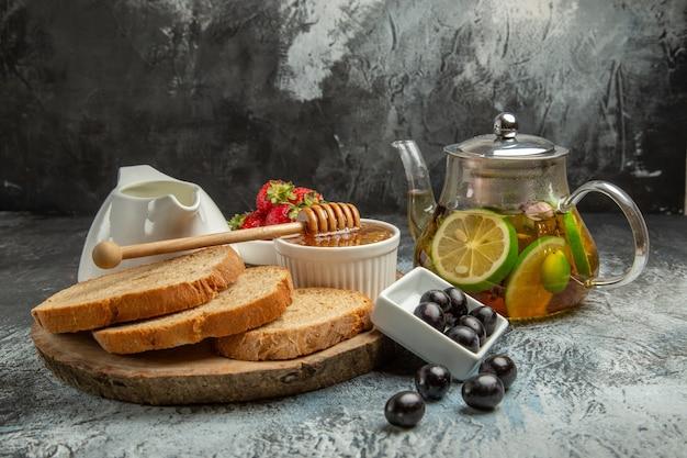 Vue de face des miches de pain avec des olives au miel et du thé sur la surface légère des aliments pour le petit-déjeuner sucré