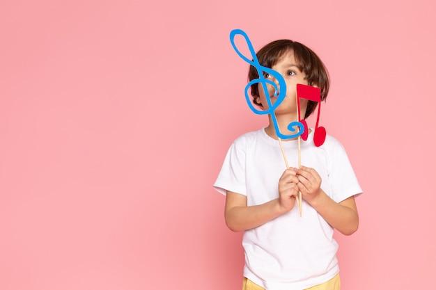 Une vue de face mignon enfant garçon en t-shirt blanc tenant des notes colorées sur l'espace rose