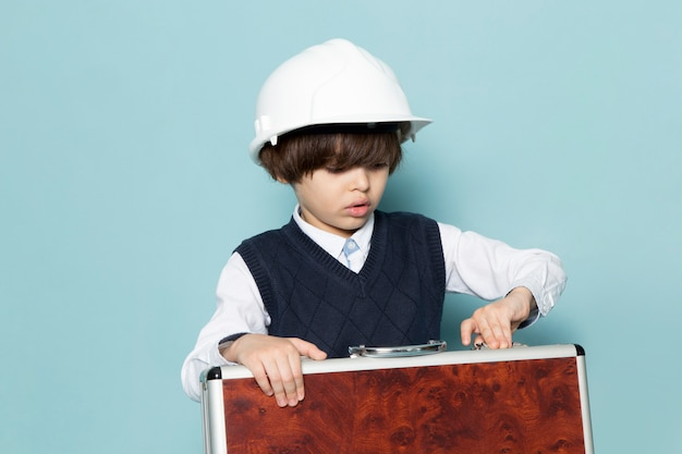 Une vue de face mignon garçon d'affaires en bleu classique chemise jamper posant tenant une valise marron-argent mode de travail d'entreprise