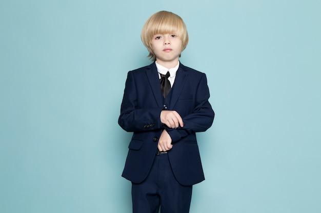 Une vue de face mignon garçon d'affaires en costume classique bleu posant la mode de travail d'entreprise