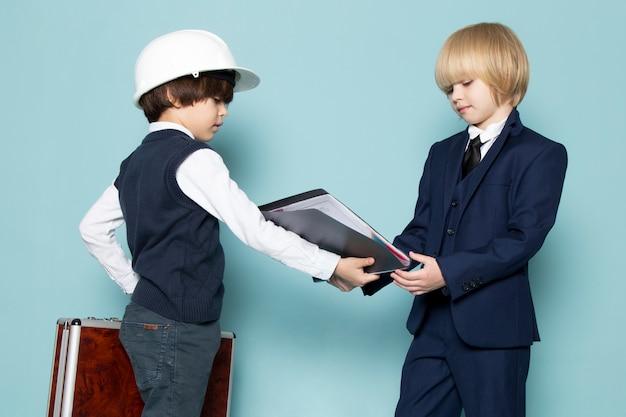 Une vue de face mignon garçon d'affaires en costume classique bleu posant tenant une valise marron-argent avec un autre garçon donnant des dossiers de mode de travail d'entreprise