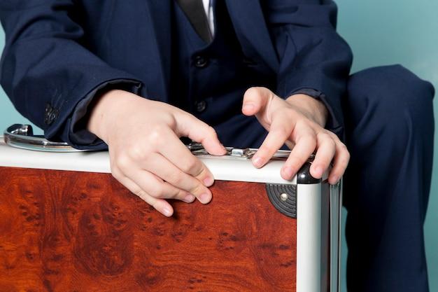 Une vue de face mignon garçon d'affaires en costume classique bleu posant tenant une valise marron-argent mode de travail d'entreprise