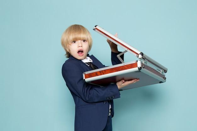 Une vue de face mignon garçon d'affaires en costume classique bleu posant tenant une valise marron-argent surpris la mode de travail d'entreprise