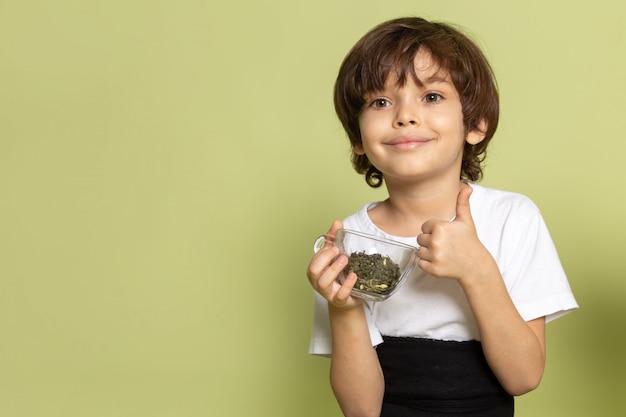 Une vue de face mignon garçon souriant tenant des espèces sur le bureau de couleur pierre