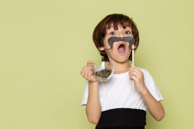 Une vue de face mignon garçon en t-shirt blanc tenant la moustache sur l'espace de couleur pierre