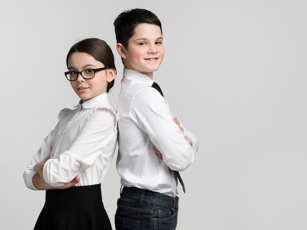 Vue de face mignon jeune garçon et fille posant ensemble