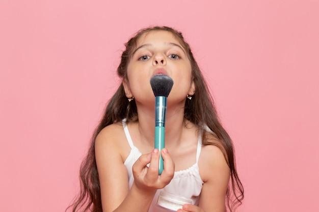 Une vue de face mignon petit enfant faisant du maquillage