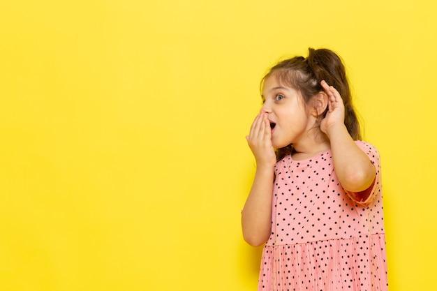 Une vue de face mignon petit enfant en robe rose chuchotant quelque chose