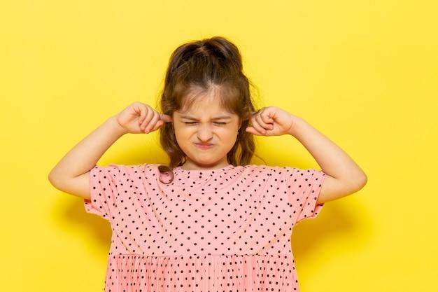 Une vue de face mignon petit enfant en robe rose couvrant ses oreilles