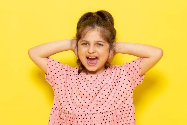 Une vue de face mignon petit enfant en robe rose crier