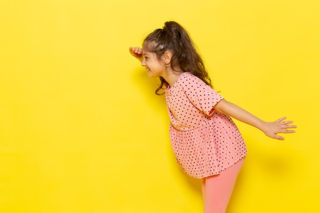 Une vue de face mignon petit enfant en robe rose à la recherche au loin