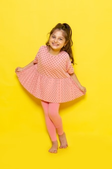 Une vue de face mignon petit enfant en robe rose souriant et posant