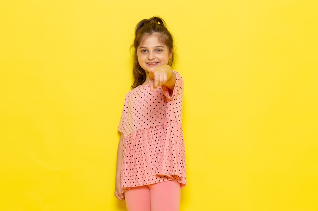 Une vue de face mignon petit enfant en robe rose souriant et soulignant