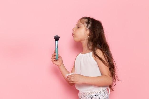 Une vue de face mignon petit enfant se prépare à faire du maquillage