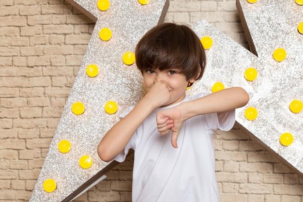 Une vue de face mignon petit enfant en t-shirt blanc jean foncé sur l'étoile conçu stand jaune et fond clair