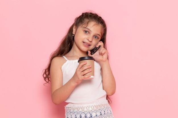 Une vue de face mignon petit enfant tenant une tasse de café et parler au téléphone