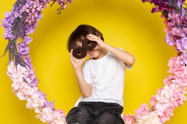 Une vue de face mignon petit garçon en t-shirt blanc tenant une paire de beignets choco sur le bureau jaune