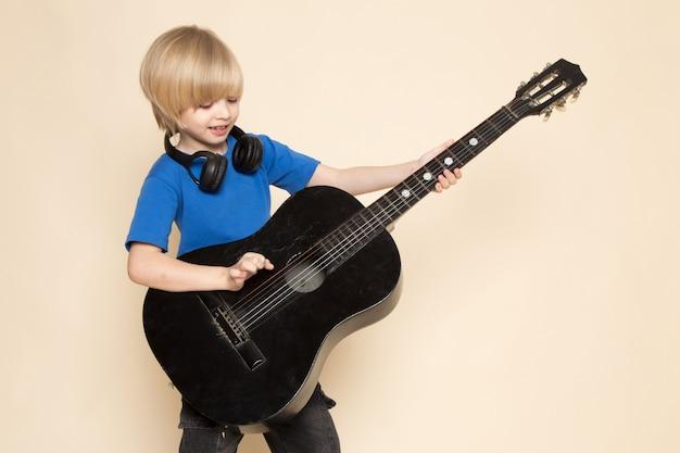 Une vue de face mignon petit garçon en t-shirt bleu avec un casque noir tenant une guitare noire