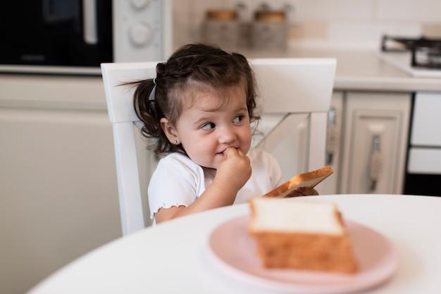 Vue de face mignonne jeune fille sur une chaise