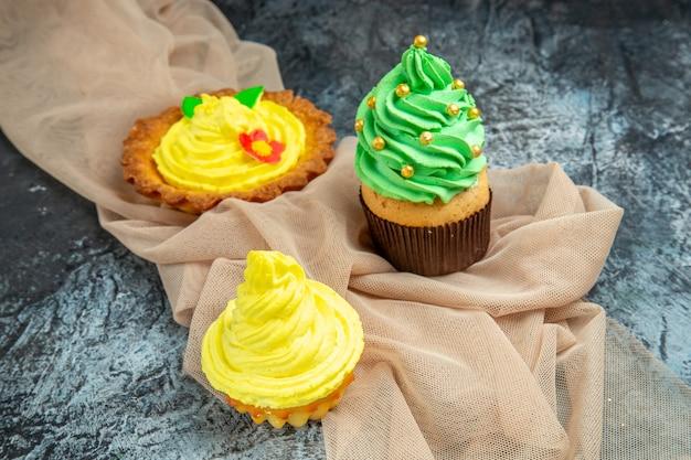 Vue de face mini châle beige biscuit cupcakes colorés sur fond sombre