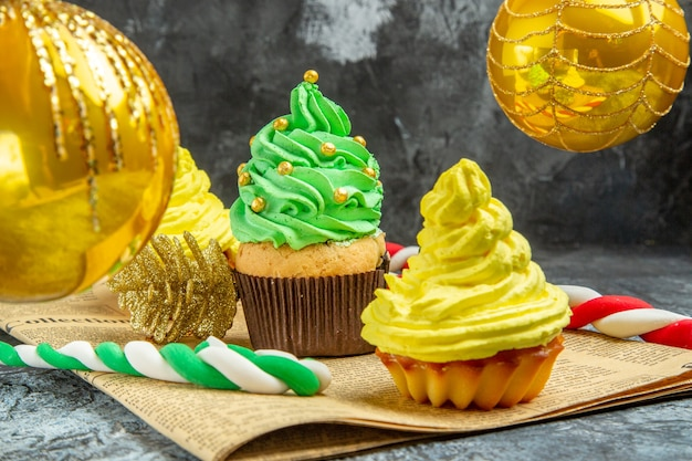 Vue de face mini cupcakes colorés boules d'arbre de noël bonbons de noël sur journal sur photo de noël sombre